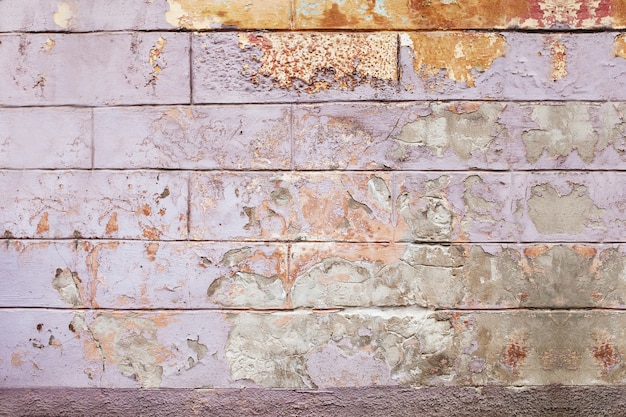 古いひびの入った壁の背景、ライラックとオレンジのペイントテクスチャが欠けています。