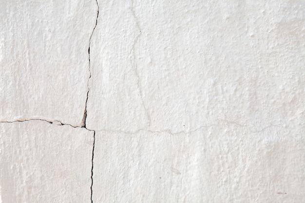 古いひびの入った白い壁の背景。
