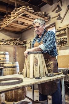 오래된 장인은 고풍스러운 방식으로 금속과 목재로 새 나무 통을 만듭니다.