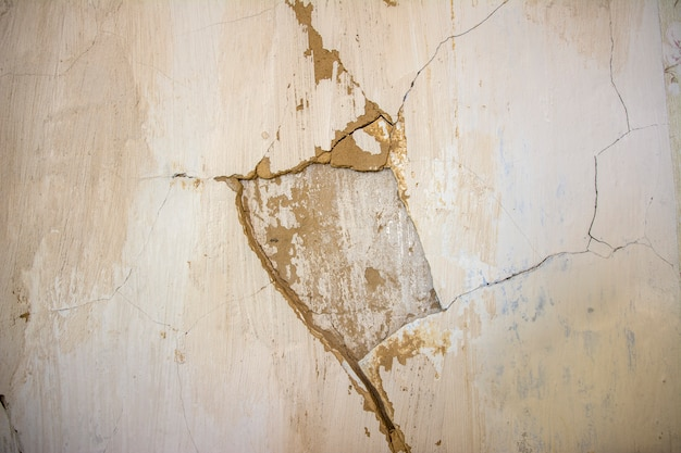 Old crumbled plaster on the wall of the house.