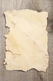Old crumpled paper on a wooden background