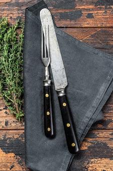 古いカトラリーナイフとフォーク。暗い木の背景。上面図。