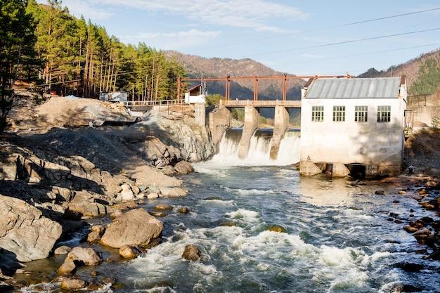 川の水力発電所の水力エネルギーに水が流れる古いダム