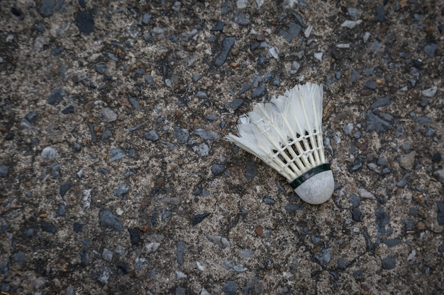 Old damage shuttlecock ,badminton ball on the floor background