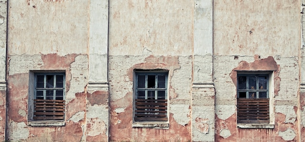 The old and damaged abandoned wall with windows with broken glass
