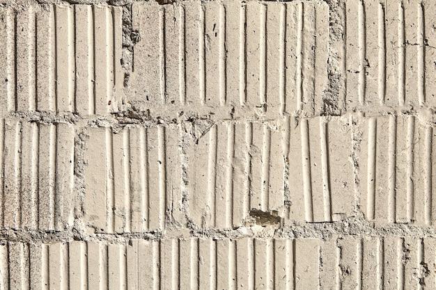 Старая поврежденная кирпичная кладка из профнастила.