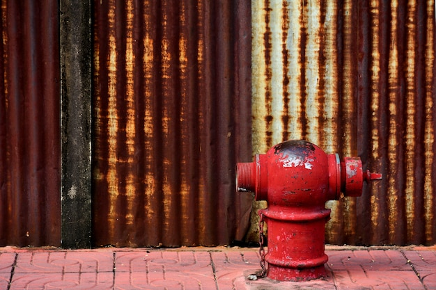 The old and damaged red fire head on pavement