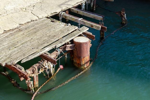 Старый поврежденный деревянный причал в морской гавани