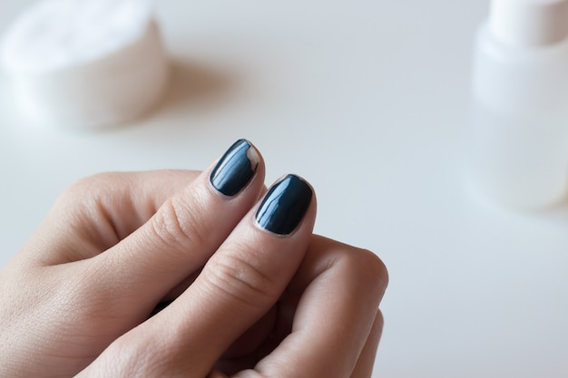 Old dark blue manicure. shabby nail polish. woman hands on white table. spa.