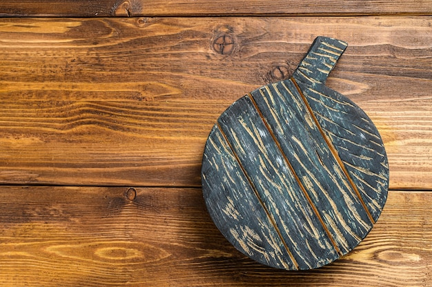 Old dark cutting board on brown wooden table.
