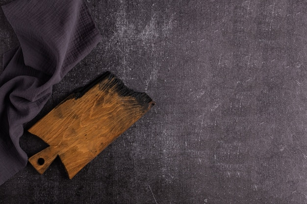 An old dark cutting board on a dark background. the board is charred