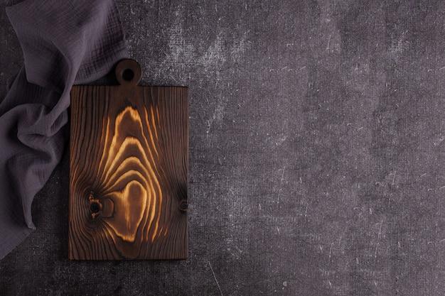 Old dark cutting board on dark background