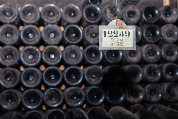 セラーの行で古い暗いほこりっぽいワインボトル