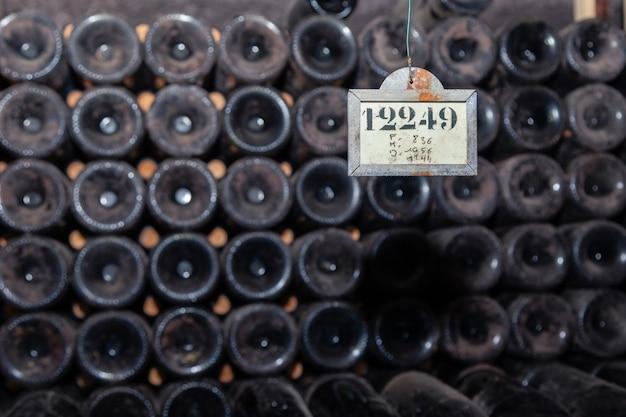 Old dark dusty wine bottles in rows in cellar