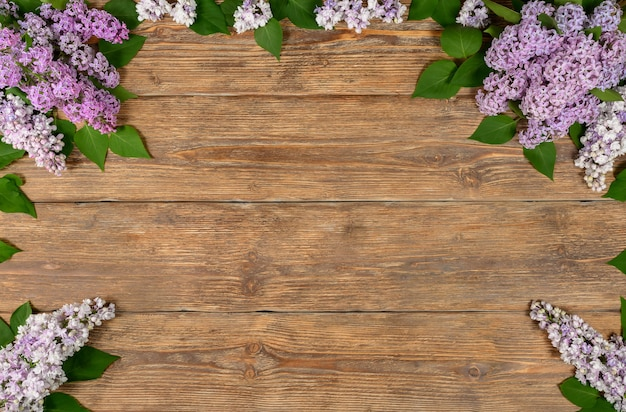 Old dark wooden background with lilac flowers copy space