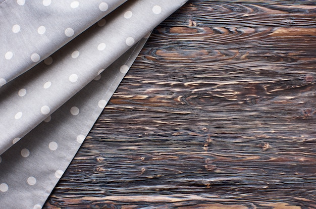 Old dark wooden background. wooden table with grey kitchen towel