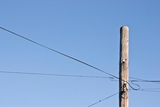 Old decrepit wooden telephone pole against a gradient blue sky