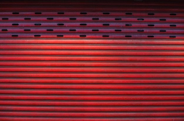 Old detailed aged vintage red textured zinc alloy metal roller shutter door, store front exterior design used in construction industry as building material.