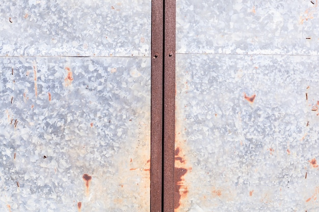 Old detailed aged vintage rusty red brown textured zinc alloy metal sheet fence door of warehouse