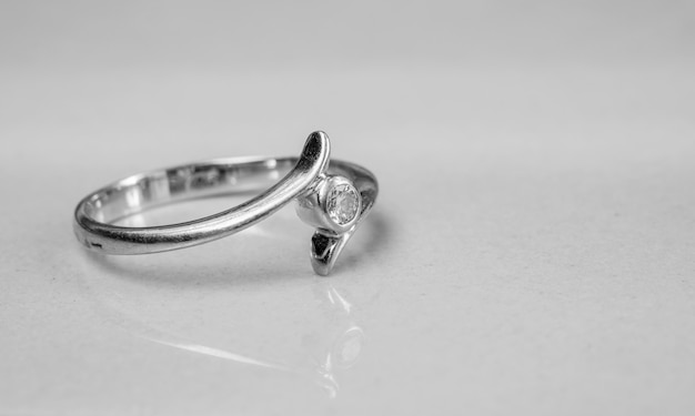 Old diamond ring on blurred marble floor