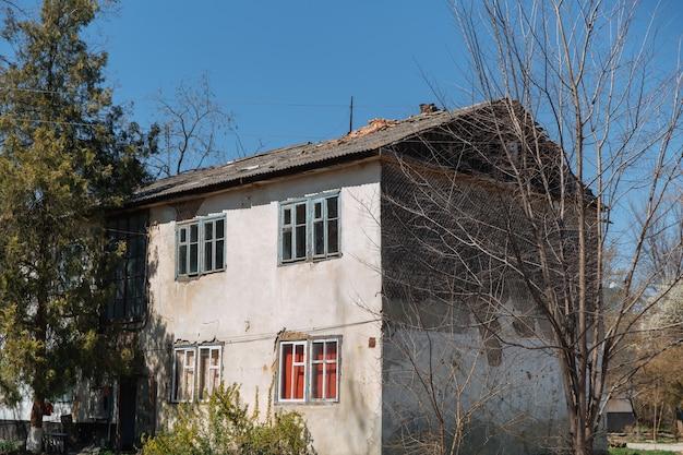 住宅問題を改修する必要がある古い老朽化した風雨にさらされた家