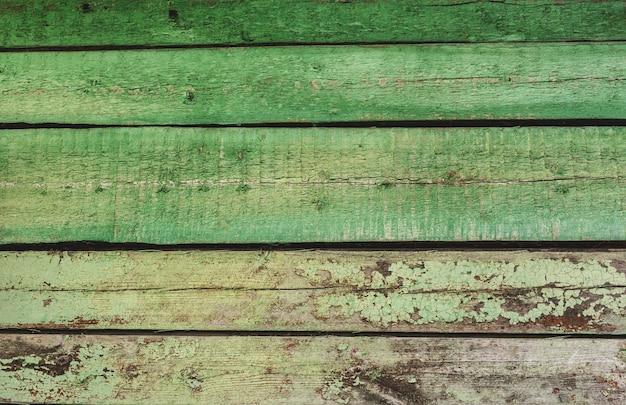 오래되고 거무스름한 표면, 퇴색된 나무에 녹색 페인트 벗겨짐. 수평 질감