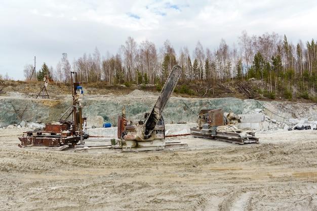 돌 블록을 처리하기 위한 오래된 더러운 띠톱 및 기타 기계는 대리석 추출을 위한 채석장에 서 있습니다.