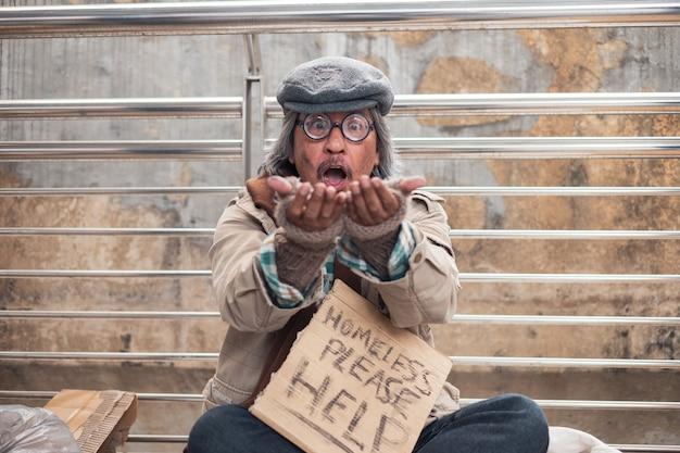 橋の上で見つめて興奮して手のひらを示す古い汚いホームレスの物乞い