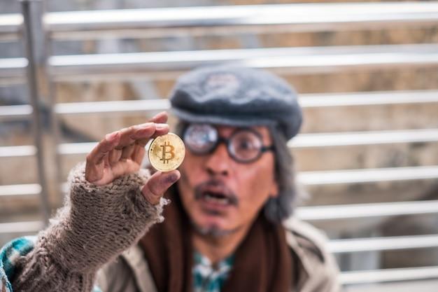 Старый грязный бездомный держит золотой биткойн с возбужденным видом