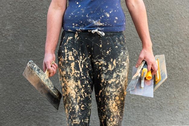 Старые грязные в штанах малярных работ на работнике со строительными инструментами на строительной площадке.