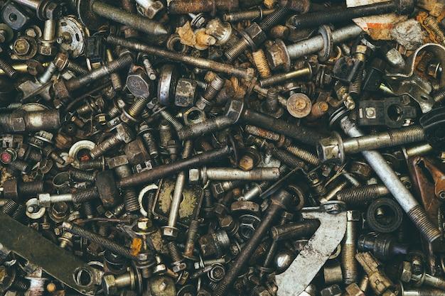 오래된 더러운 믹스 너트와 볼트는 차고 산업 배경을 위한 그리스 오일 텍스처 패턴으로 그런지를 사용했습니다.