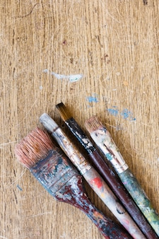 Old dirty paint brushes on weathered wooden backdrop