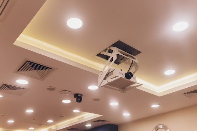Old and dirty projector hang on ceiling in meeting room, education concept.