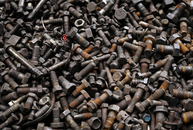 Old dirty rusty screw, bolt, metal pin and metal nuts background.