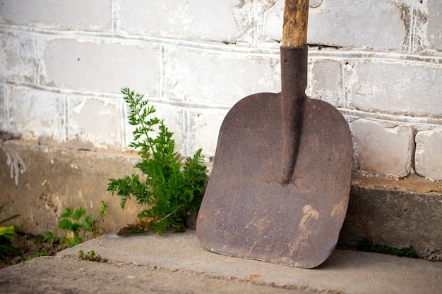 Old dirty shovel used leaning on brick white wall