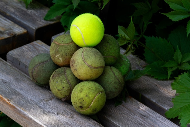Old dirty tennis balls are laid out on bench in the shape of pyramid