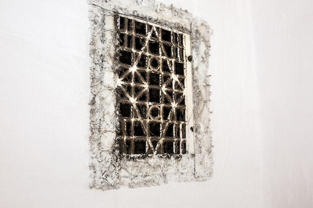 古い汚れた壁のバスルームのファンベント。復元プロセス。メンテナンス修理はフラットで改修工事を行います。危険なほこりやカビ。