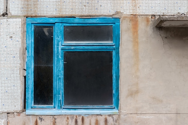 Old dirty window in blue wooden frame in abandoned house