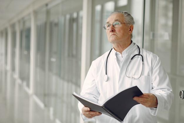 Старый доктор в униформе стоит в зале