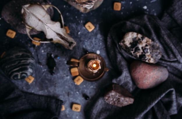 Старый череп собаки горящая свеча деревянные руны и камни на столе ведьм