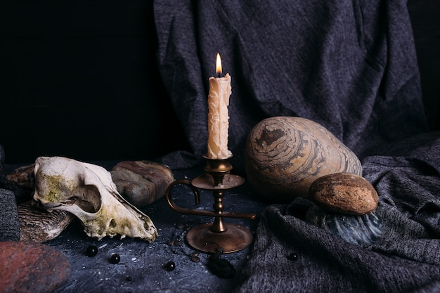 Old dog skull burning candle wooden runes and stones on the witch table