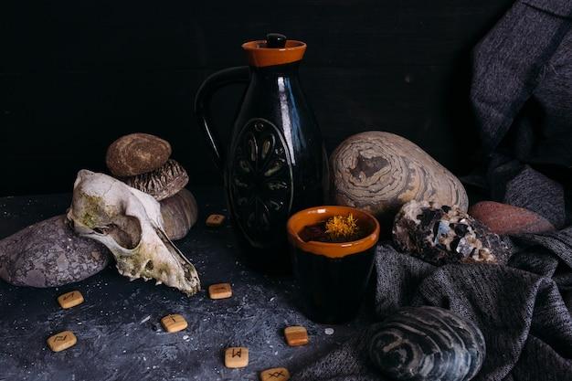 Старый кувшин из черепа собаки и камни на столе ведьм заколдованный напиток с лепестками цветов