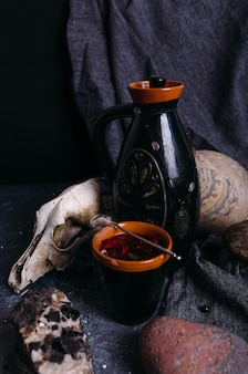 Old dog skull jug and stones on witch table enchanted drink with flower petals