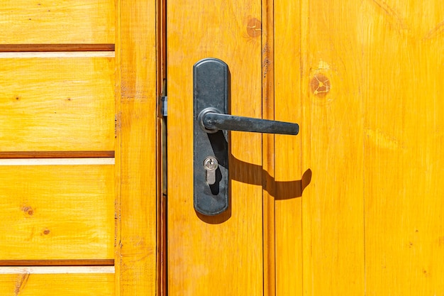 Old door handle with lock on the wooden door