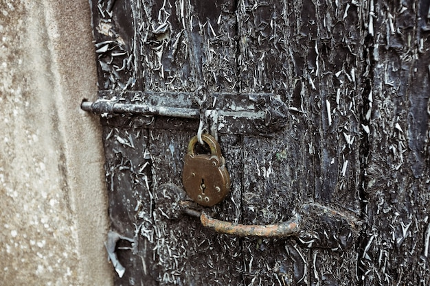 Old door with paint peelings and lock
