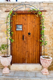 Old door with tubs for flowers standing near