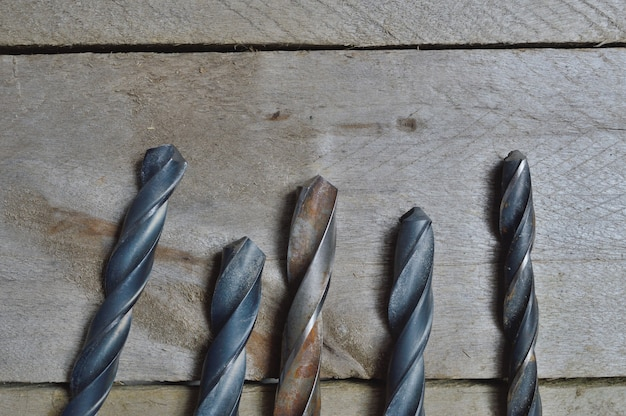 Old drills lie on a wooden board. view from above.