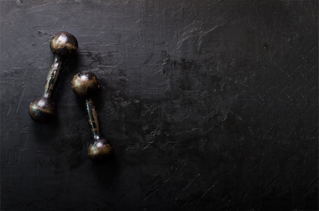 Old dumbbells on concrete background. sport concept. free space for your text.