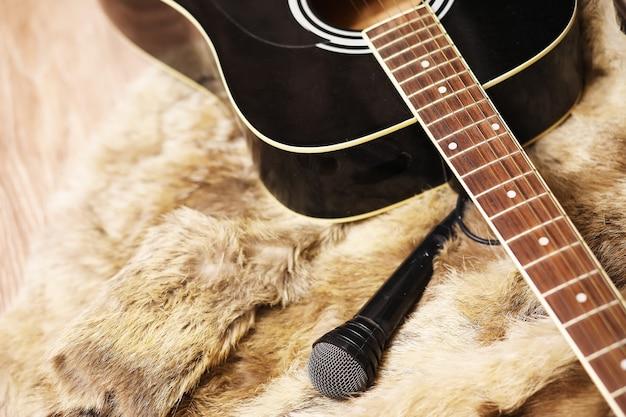 Old dusty acoustic cutaway guitar on a floor. spruce dreadnought acoustic guitar. guitar on fur background.