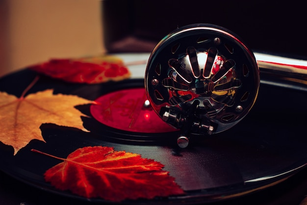 Old dusty gramophone playing a vinyl record at autumn time